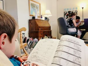 Little brother Cyder reading during Merckx Dascomb's piano lesson.  Photo credit: Tatiana Johnson